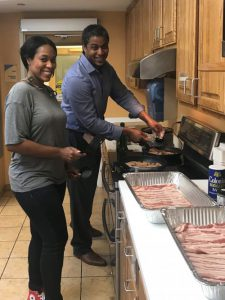 Two of our staff preparing bacon for dinner.